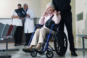 Senior woman on wheelchair with her husband and doctors analyzing x-ray in background.